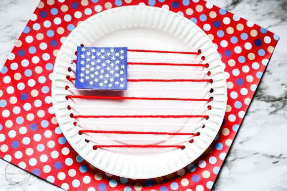 American Flag made our of red and white yarn and paper plates