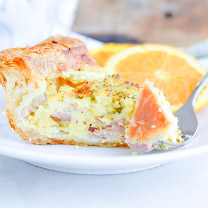 Quiche made with Puff Pastry, served with an orange, on a white plate.