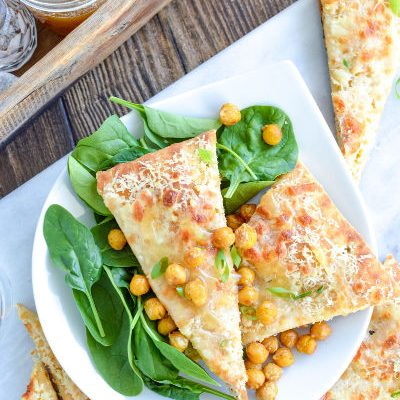 Flatbread with oil drizzled on top with chickpeas and spinach