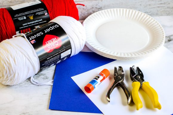 Red yarn, white yarn, paper plates, hole punches, and glue stick