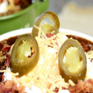 Bowl of chili topped with sour cream, shredded cheese, and jalapenos