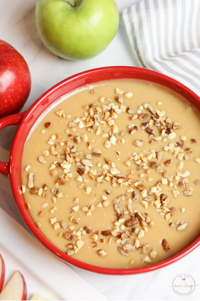 Creamy Caramel Apple Dip topped with nuts in a red bowl