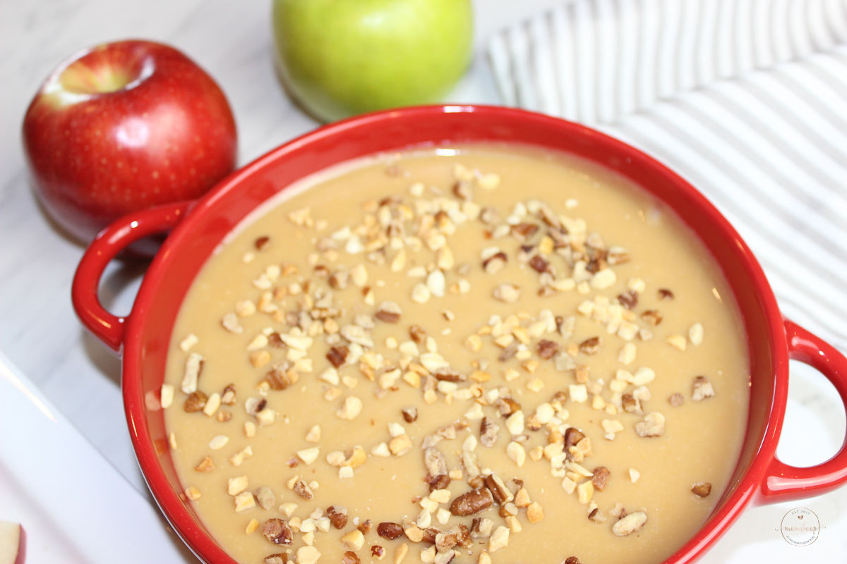 Caramel Apple Dip with chopped nuts in a red bowl