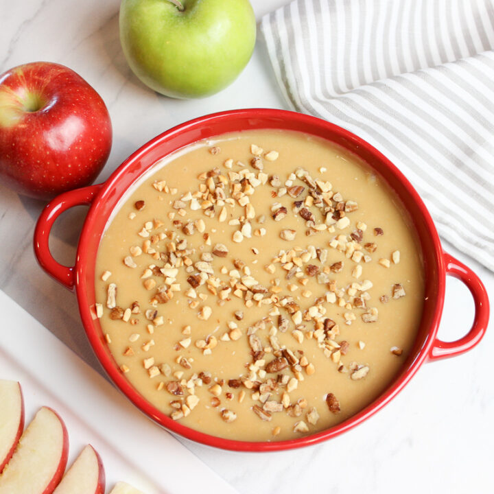 Apple slices with creamy caramel dip in a red bowl